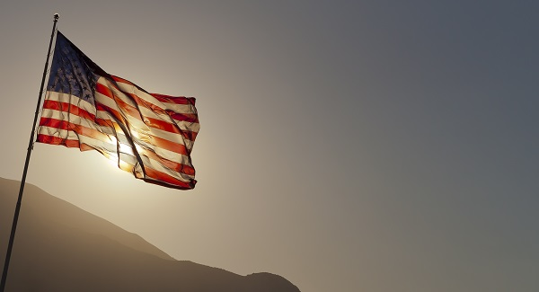 American Flag flying in the wind with sun behind it