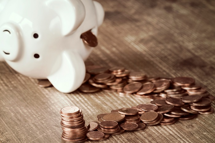 White piggy bank tipped over with pennies pouring out