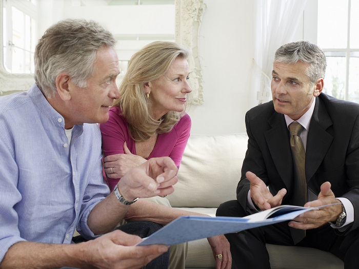 Mature couple speaking with business man