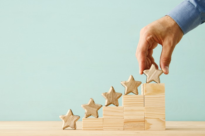 Hand putting stars on a staircase structure