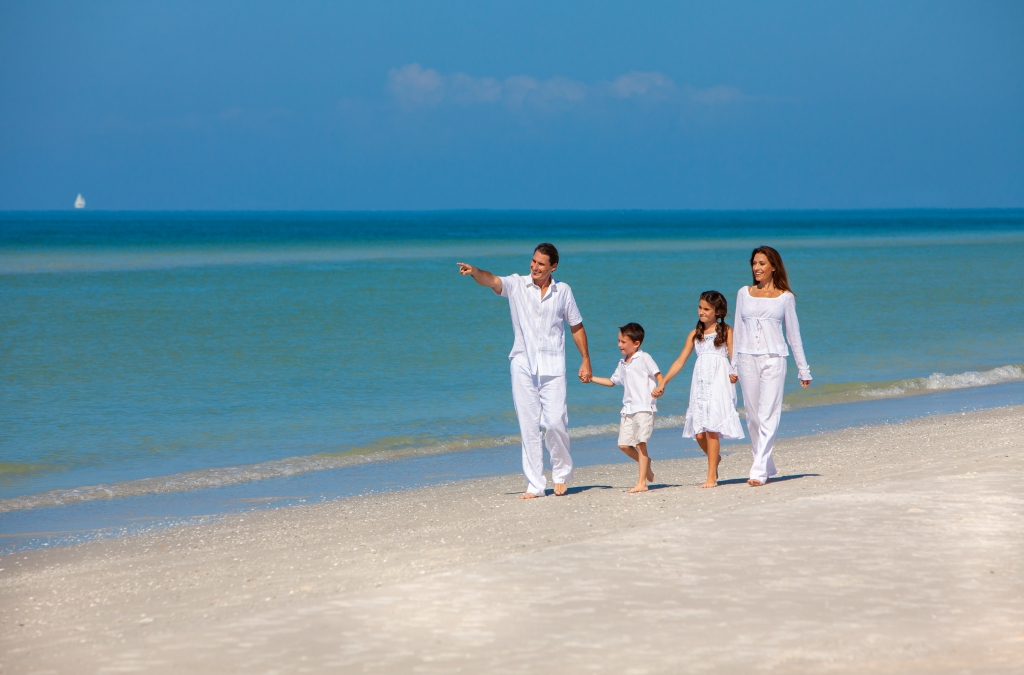 Family wearing white walking on a beach