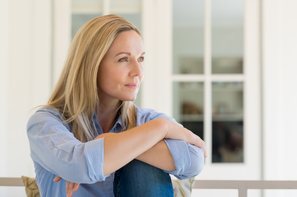 Woman sitting in home thinking